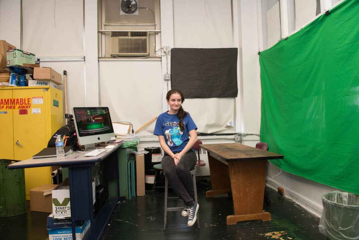 Elsa Nilay, a senior at Hamtramck High School, helps direct the school's daily news programming. A makeshift green screen stretches across a wall to her left.