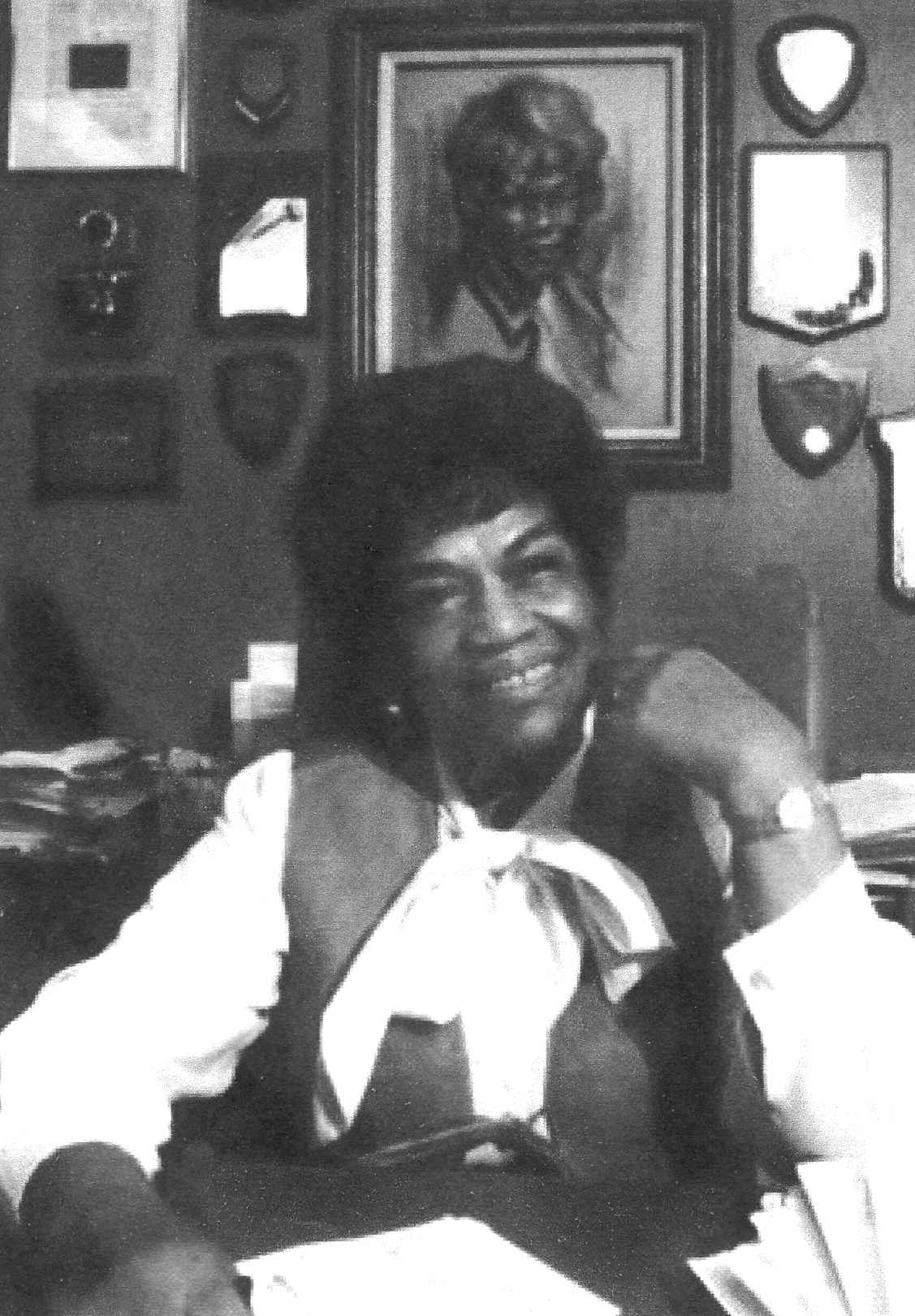 Black and white portrait of Erma Henderson sitting before a wall of portraits and plaques